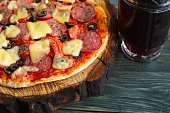 Delicious pizza with salami, mozzarella and olives and mug of dark beer, close up. Homemade culinary, snacks concept