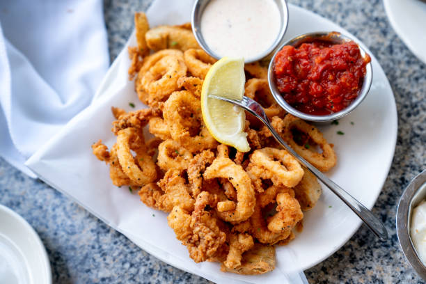 A Delicious Plate Of Deep Fried Calamari, Squid Fried To Perfection Cajun Style, Served With A Side Of Freshly Made Garlic Aioli Sauce And Cocktail Sauce, Fresh Lemon Wedges On The Side stock photo