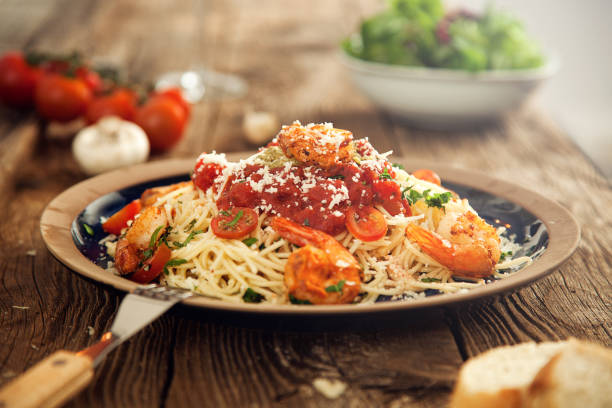 A delicious plate of shrimps on spaghetti with tomato and cheese stock photo