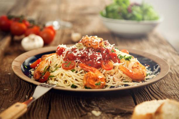 einen leckeren teller mit garnelen auf spaghetti mit tomaten und käse - weinsoße stock-fotos und bilder