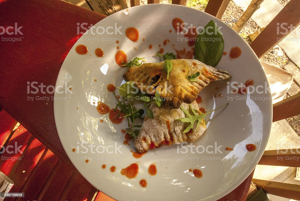 Delicious plated Spanish Empanadas Entre with hot sauce stock photo