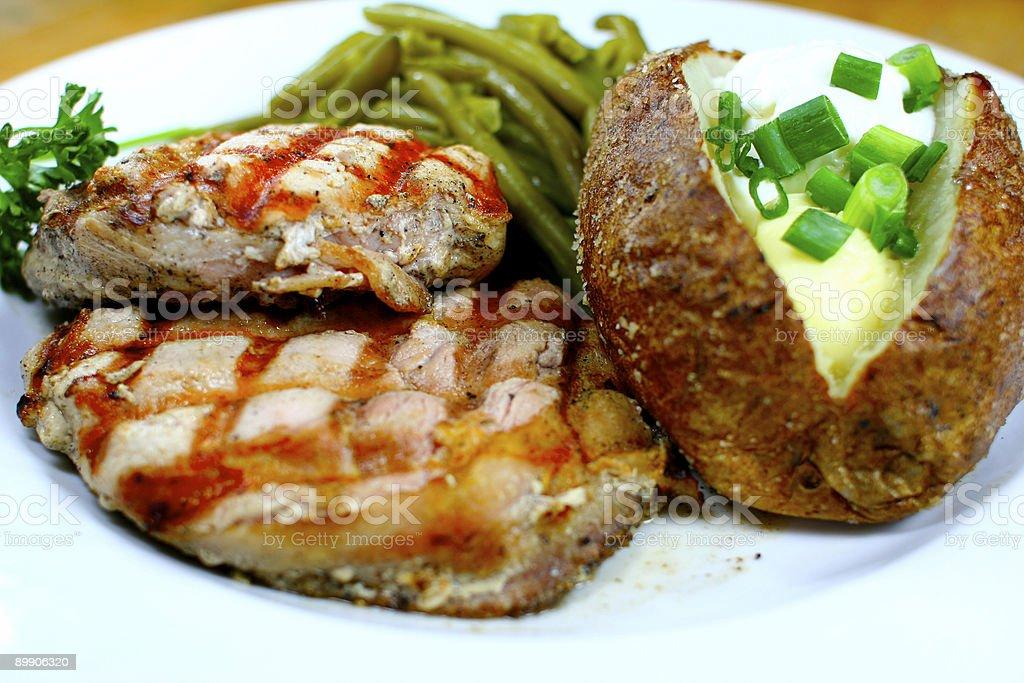 Köstliche Schweinekotelett Mahlzeit mit einer Ofenkartoffel Lizenzfreies stock-foto