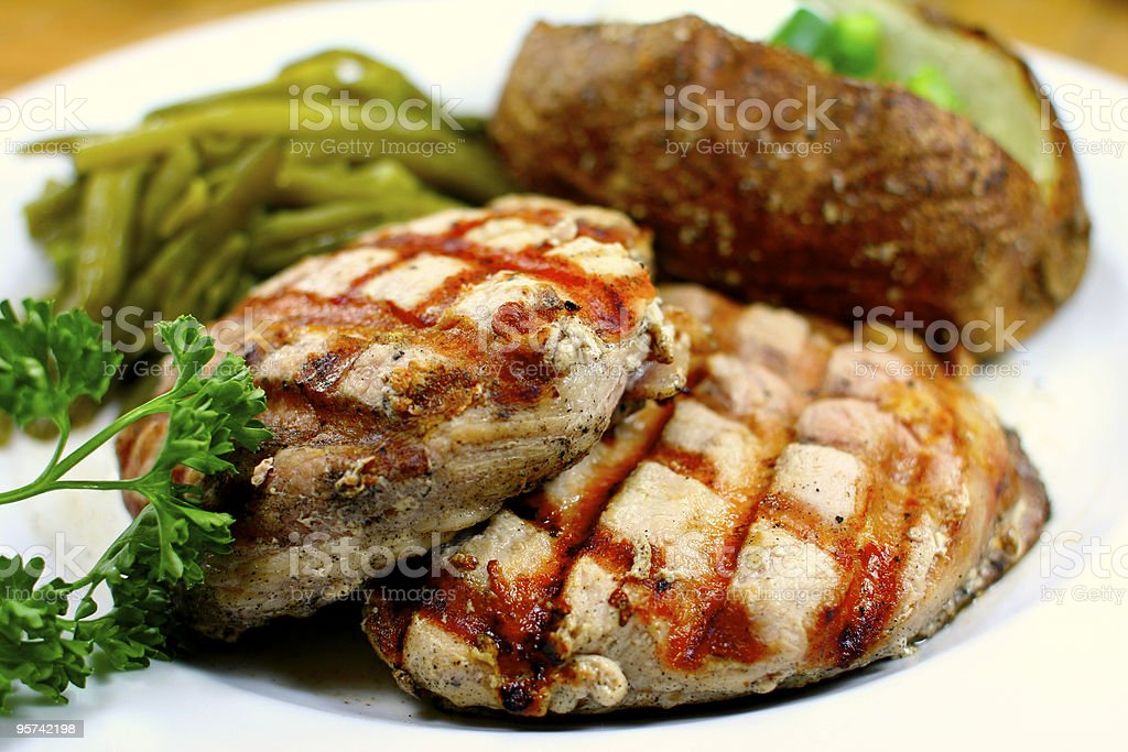 Delicious pork chop meal with a baked potato royalty-free stock photo