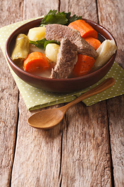 Delicious Pot-au-feu beef soup with vegetables close up in a bowl. vertical Delicious Pot-au-feu beef soup with vegetables close up in a bowl on the table. vertical pot au feu stock pictures, royalty-free photos & images
