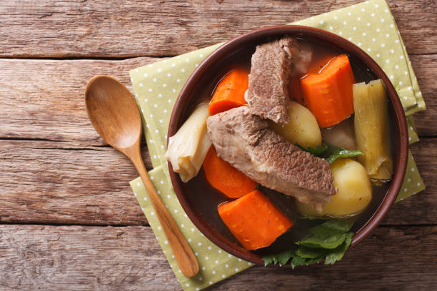 Delicious Pot-au-feu beef soup with vegetables close up in a bowl. horizontal top view Delicious Pot-au-feu beef soup with vegetables close up in a bowl on the table. horizontal view from above pot au feu stock pictures, royalty-free photos & images