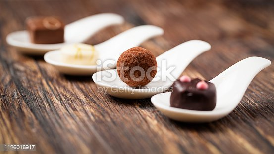 delicious pralines on spoons on wooden surface