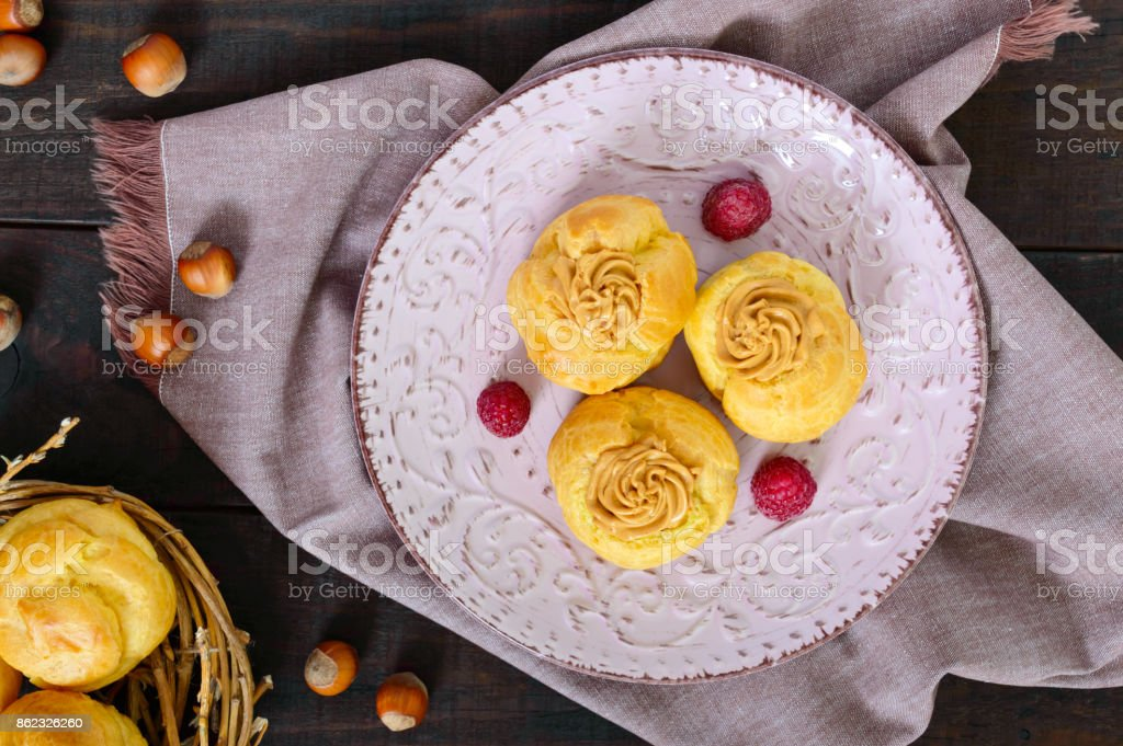 Delicious profiteroles with caramel nut cream on a ceramic plate on a dark wooden background. Top view. stock photo