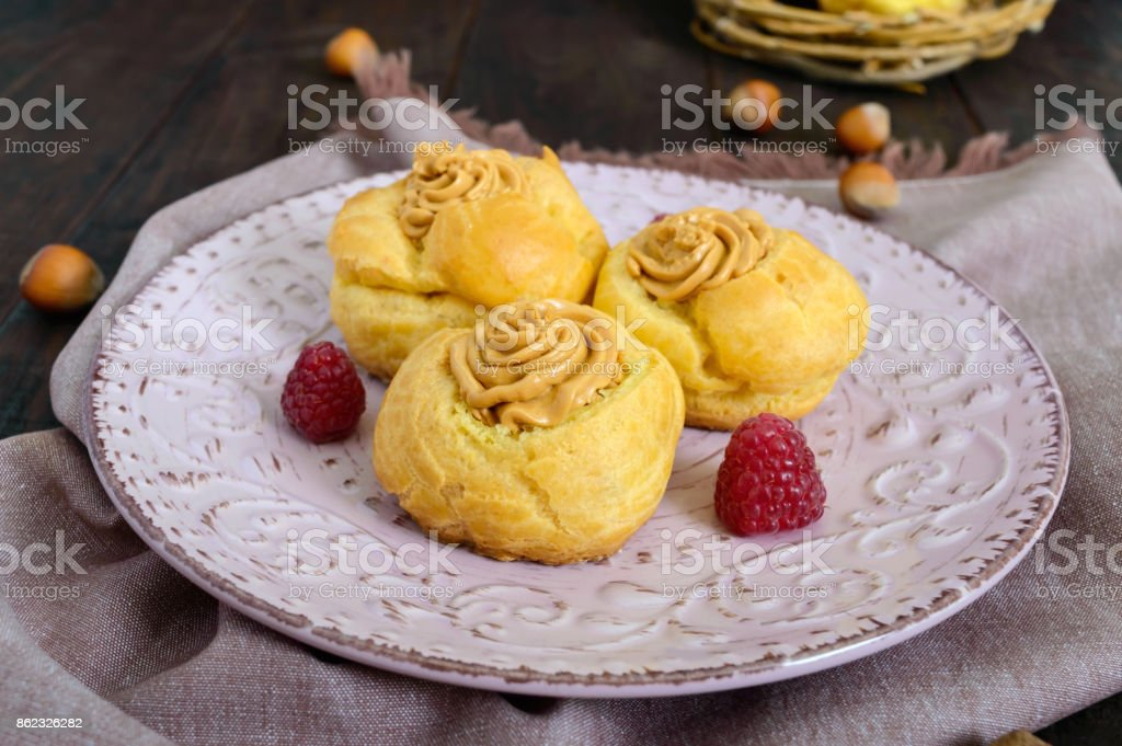 Delicious profiteroles with caramel nut cream on a ceramic plate on a dark wooden background. stock photo