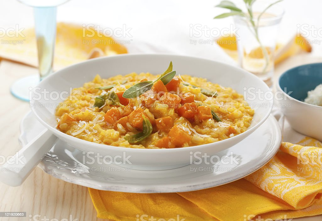 Delicious pumpkin risotto in a white bowl on wooden table stock photo
