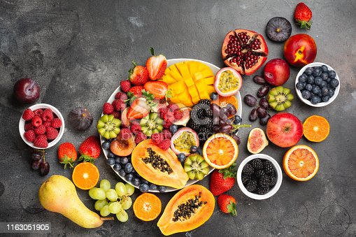 Delicious fruit platter mango pomegranate raspberries papaya oranges passion fruits berries on oval serving plate on dark concrete background, selective focus, top view, copy space