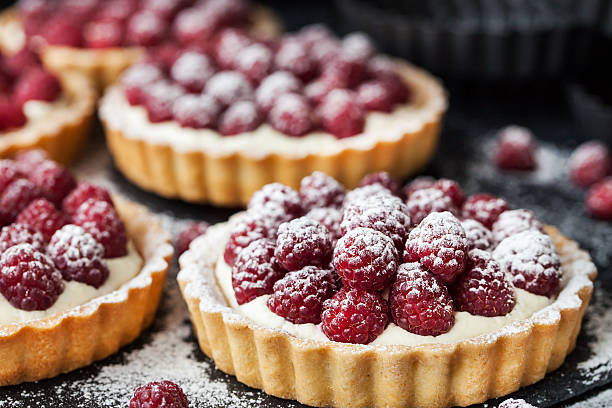 delicious raspberry mini tarts on dark background - tatlı stok fotoğraflar ve resimler