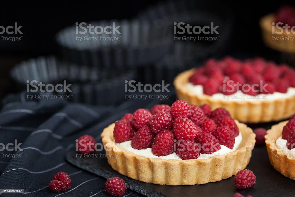 Delicious raspberry mini tarts on dark background stock photo