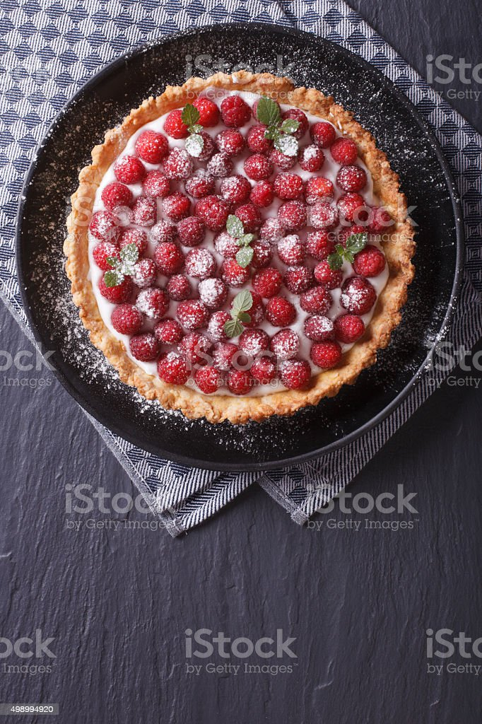 Delicious raspberry tart with cream and mint vertical top view stock photo
