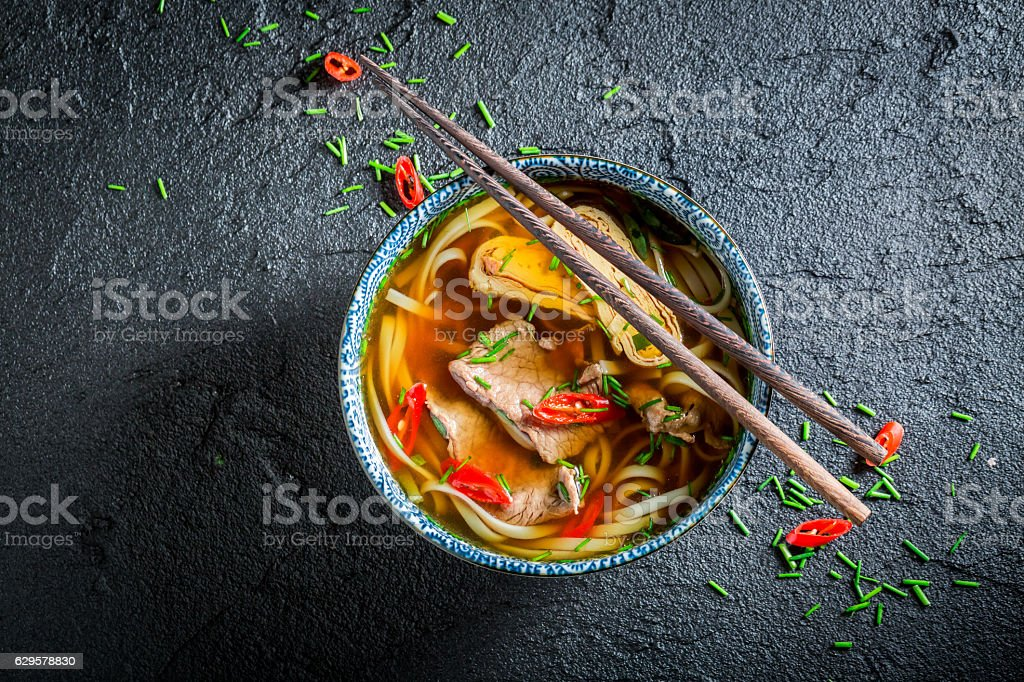 Delicious Red Curry soup in black bowl with chopsticks stock photo