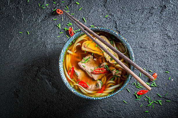 delicious red curry soup in black bowl with chopsticks - chinesisches essen stock-fotos und bilder