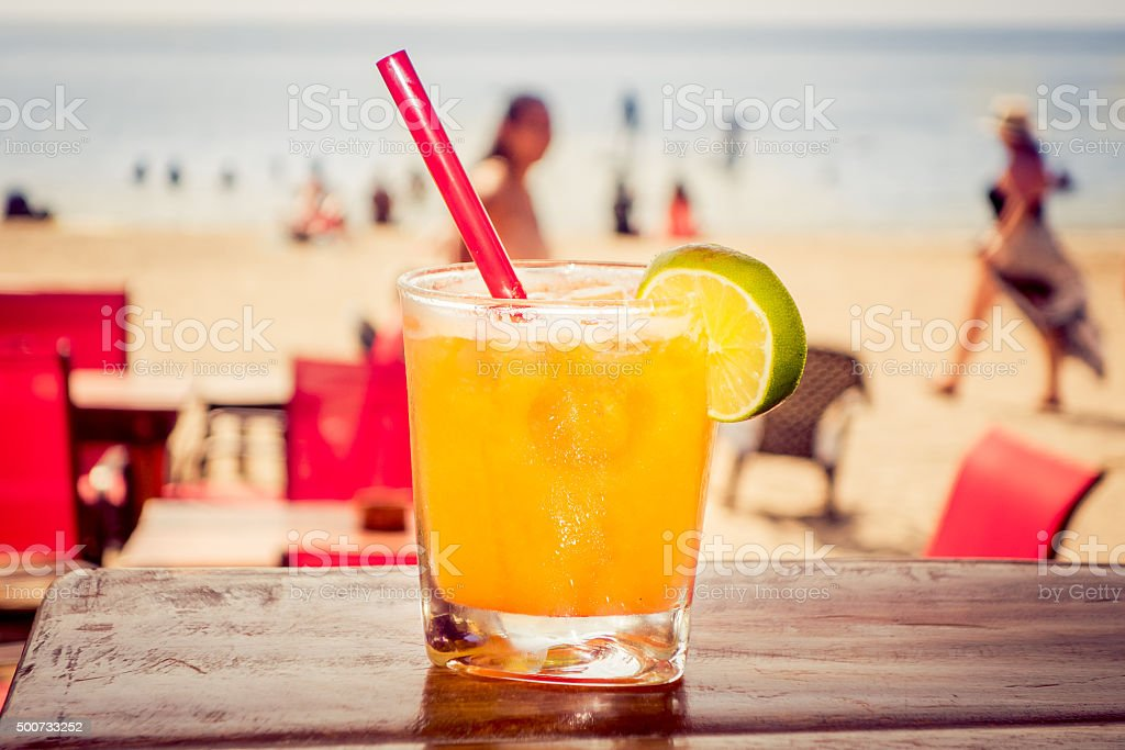 Delicious refreshing yellow cocktail with beach in the background stock photo