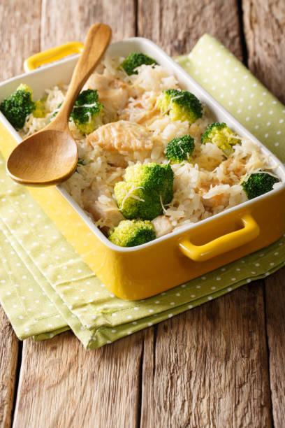 lecker reis mit hähnchen, brokkoli und käse nahaufnahme in eine auflaufform legen. vertikal - huhn brokkoli auflauf stock-fotos und bilder