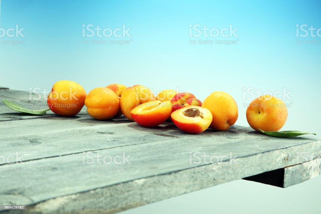 Heerlijke rijpe abrikozen op houten tafel. Vers gesneden vruchten abrikoos - Royalty-free Abrikoos Stockfoto