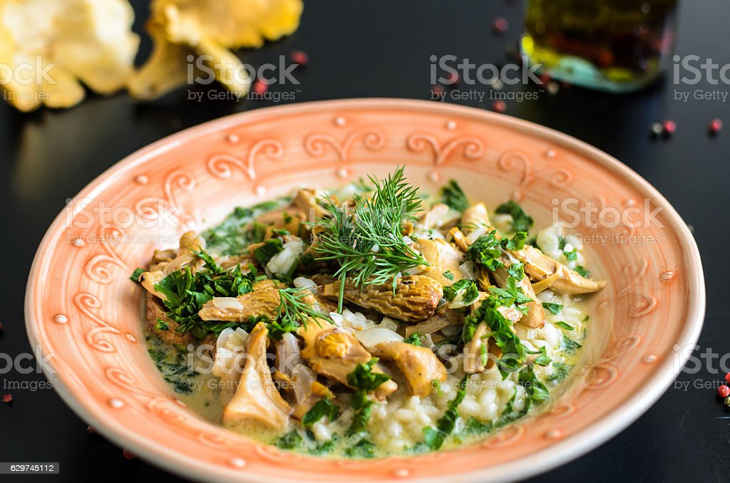 Delicious risotto with chanterelle mushrooms over rustic black background stock photo
