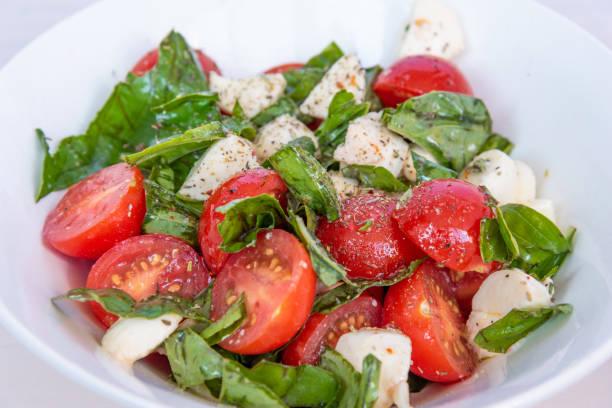 Deliciosa salada Caprese de tomate cereja e mussarela com manjericão close-up - foto de acervo