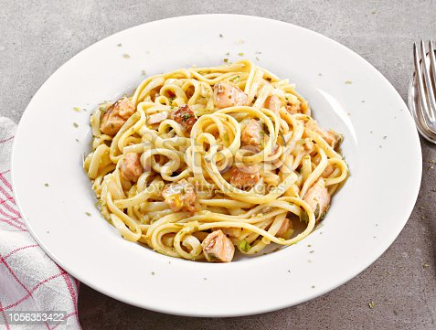 Delicious salmon pasta dish, tagliatelle or linguine noodles. High angle view of fresh spaghetti pasta with herbs and grilled salmon filet.