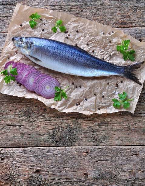 Delicious salted herring with red onion, salt and pepper on the old wooden background. Rustic style. stock photo