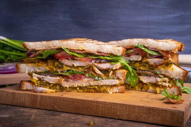Sanduíche delicioso cortado em triângulos-pão torrado com peito de galinha, bacon fritado, vegetais, pickles com mostarda e close up da rúcula em um fundo escuro, espaço da cópia - foto de acervo