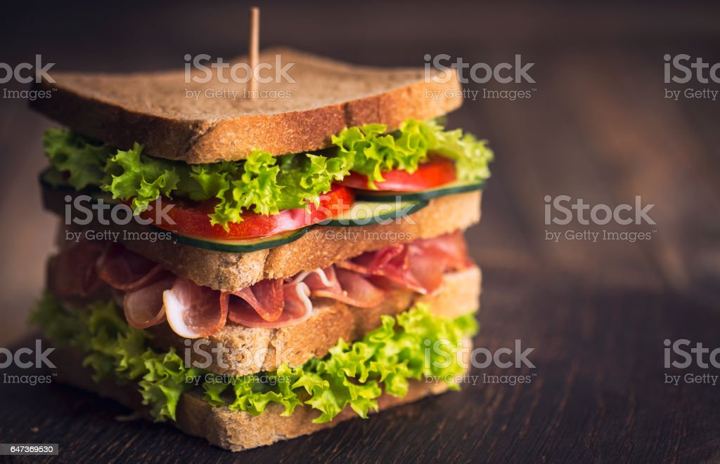 Delicious sandwich with ham, cheese, bacon and lettuce stock photo