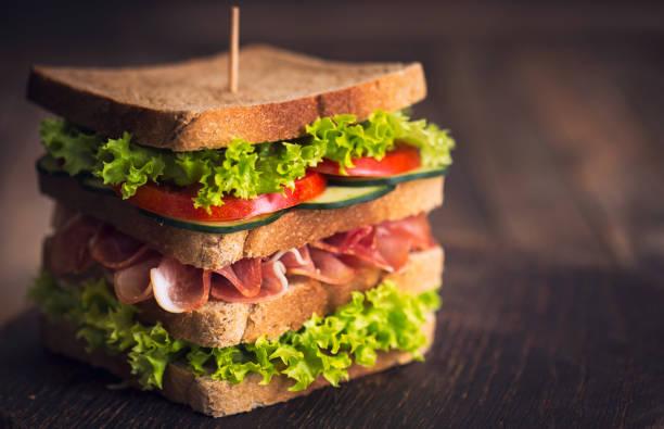 delicious sandwich with ham, cheese, bacon and lettuce - panino ripieno foto e immagini stock