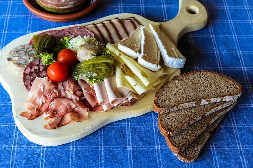 Delicious sausage and cheese plate perfectly garnished and cooked on a wooden board