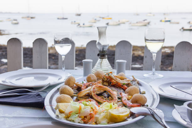 Delicious seafood menu with salad and small potatoes on silver tray with sea view and boats on background stock photo