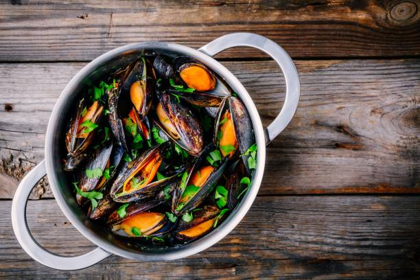 moules de délicieux fruits de mer avec sauce et le persil.  citron et baguette. palourdes dans leur coquille. - moules photos et images de collection