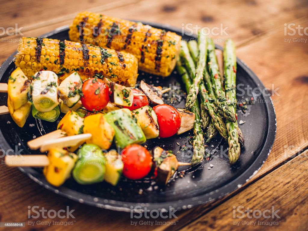 Delicious selection of grilled vegetable kebabs, corn and asparagus stock photo