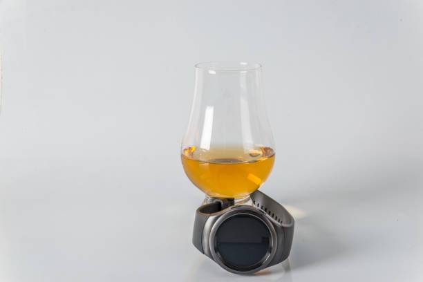 leckeres single malt whiskey-glas mit smartwatch auf weißem hintergrund - q q armbanduhr stock-fotos und bilder