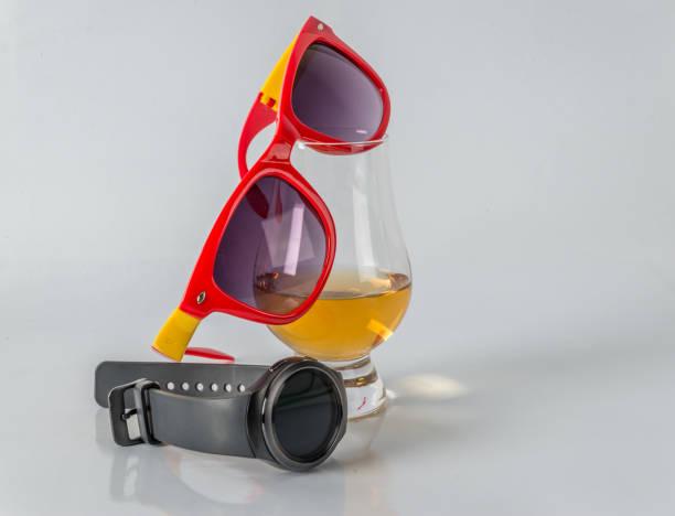 leckeres single malt whiskey-glas mit sonnenbrille auf weißem hintergrund, smartwatch - q q armbanduhr stock-fotos und bilder