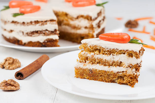 Delicious slice of carrot sponge cake with icing cream and stock photo