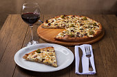 istock Delicious slice served on the plate. Meat pizza on wooden board. Made with Mozzarella, picanha meat, onion, cheese, sauce and olives. Filet Steak. Fork and Knife Top. glass of red wine. Horizontal. 1240628262