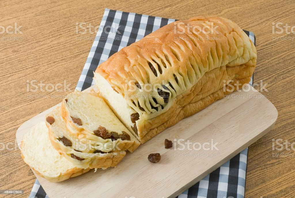 Delicious Sliced Raisin Bread on Wooden Cutting Board stock photo