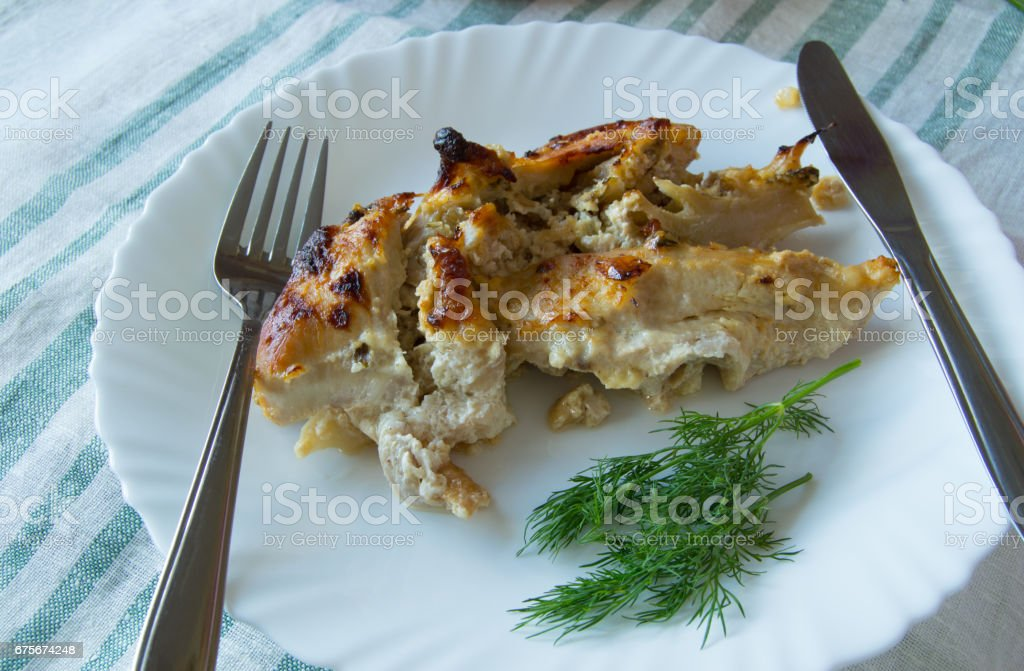 Delicious slices of baked chicken breast and Cutlery on linen napkin royalty-free stock photo