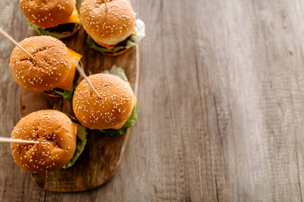 Delicious slider-burgers on dining table Close up of homemade cheeseburgers on wooden tray served on dining table, directly above slider burger stock pictures, royalty-free photos & images
