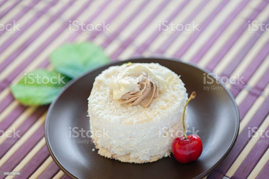 Pequeno delicioso bolo de coco e cerejas em um prato - foto de acervo