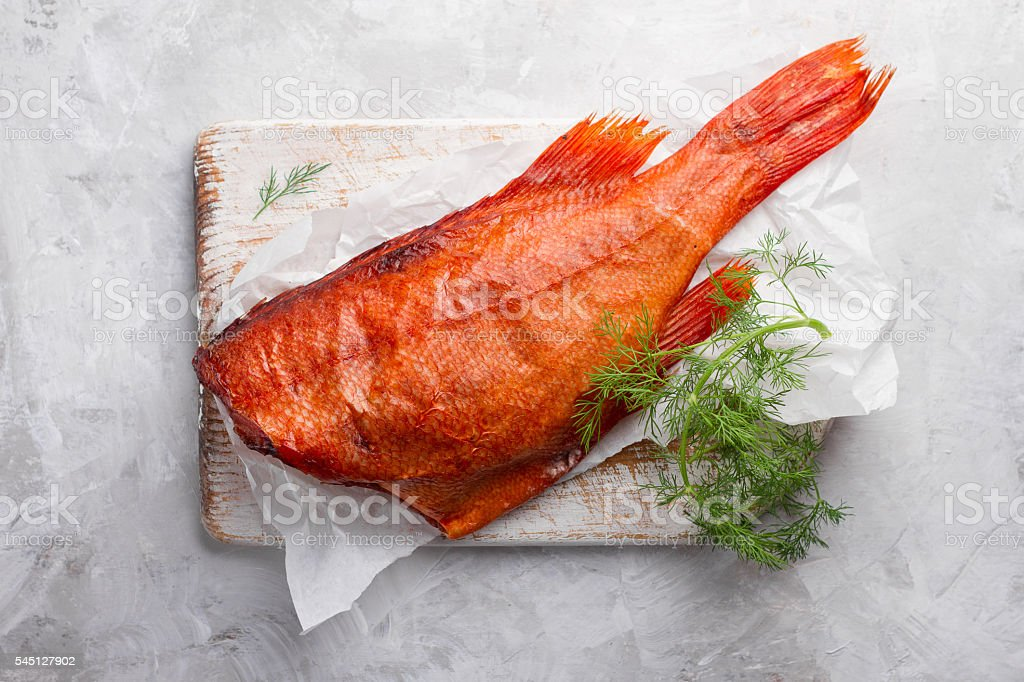 Delicious smoked fish (ocean perch) on wooden background stock photo