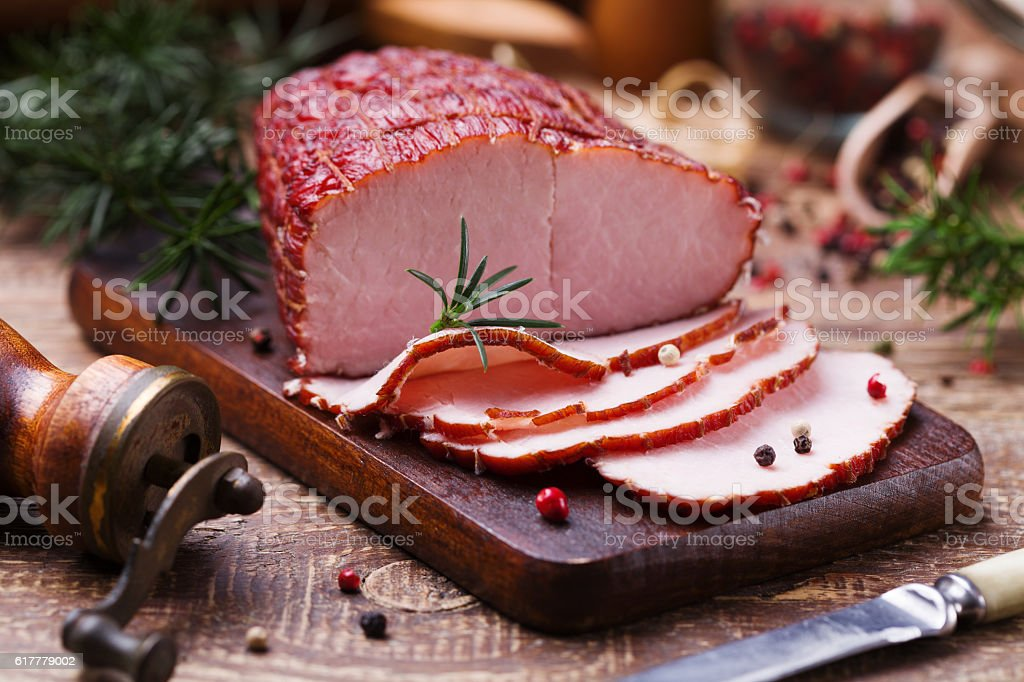 Delicious smoked ham on a wooden board with spices. stock photo