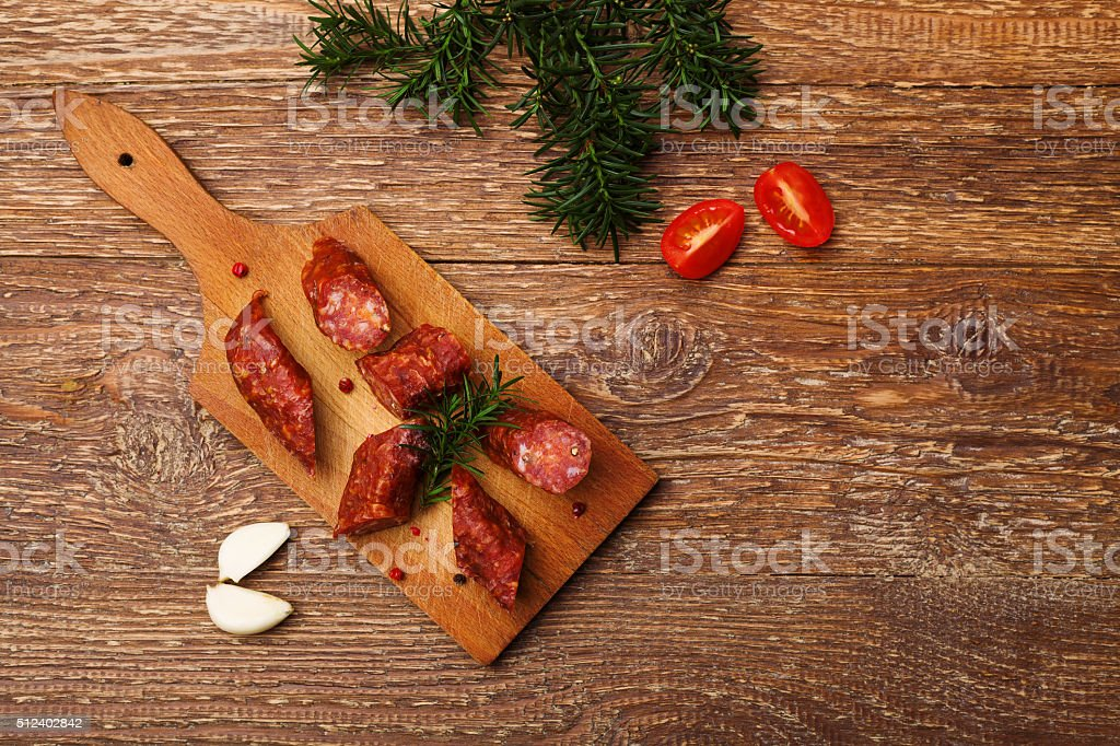 Delicious smoked sausage, sliced on a wooden board with spices. stock photo