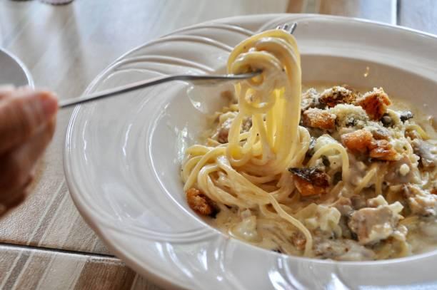leckere spaghetti carbonara auf holztisch - pasta cabonara stock-fotos und bilder