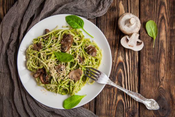 leckere spaghetti-teller mit spinatsauce und champignons - spaghetti mit spinat stock-fotos und bilder