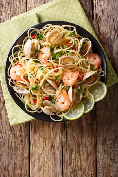 läcker spaghetti pasta med musslor, räkor och gröna närbild. vertikala ovanifrån - pasta vongole bildbanksfoton och bilder
