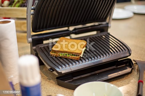 delicious square grilled sandwich lies in the open electric grill close-up, soft focus, background in blur