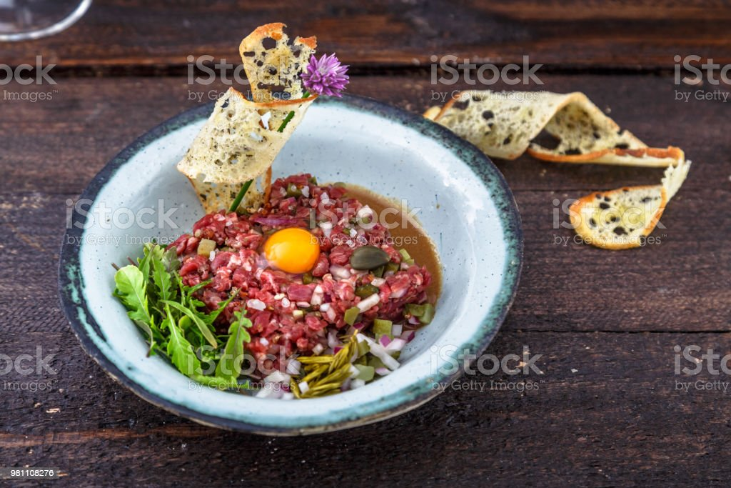 Delicious steak tartare with yolk, capers, green onion and bread stock photo