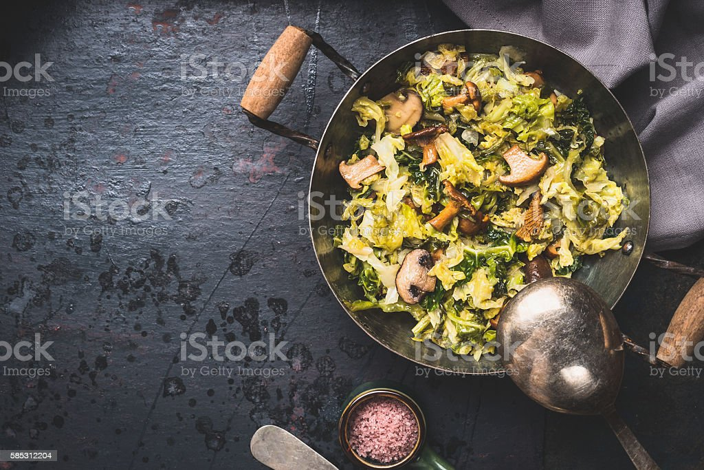 Delicious stewed cabbage with mushrooms in cooking pan stock photo